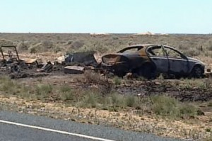 Shows burned out car on side of road on Sturt Highway